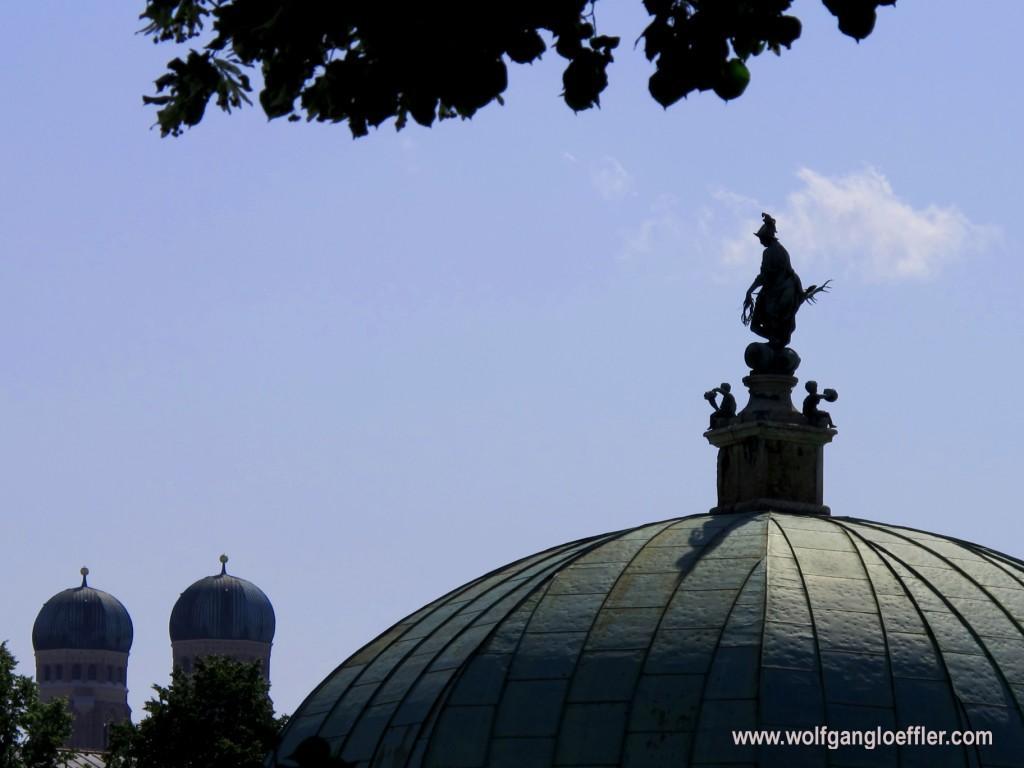 Blick auf einen Pavillon mit Statue und die Türme der Münchner Frauenkirche