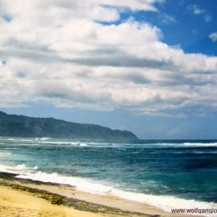 Blick vom Strand über das Blaue Meer auf eine Bergkette in der Ferne
