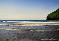 kleine Wellen plätschern auf einen schwarzen Strand