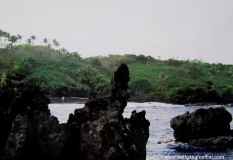 schwarze Lavafelsen ragen aus dem Meer an einem Strand auf Mauiui