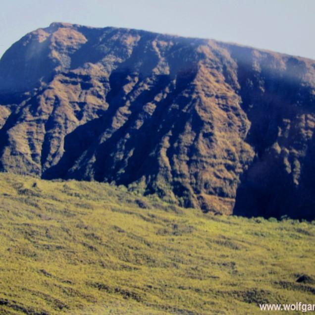 Luftaufnahme einer Felswand, die aus einem Wald emporragt