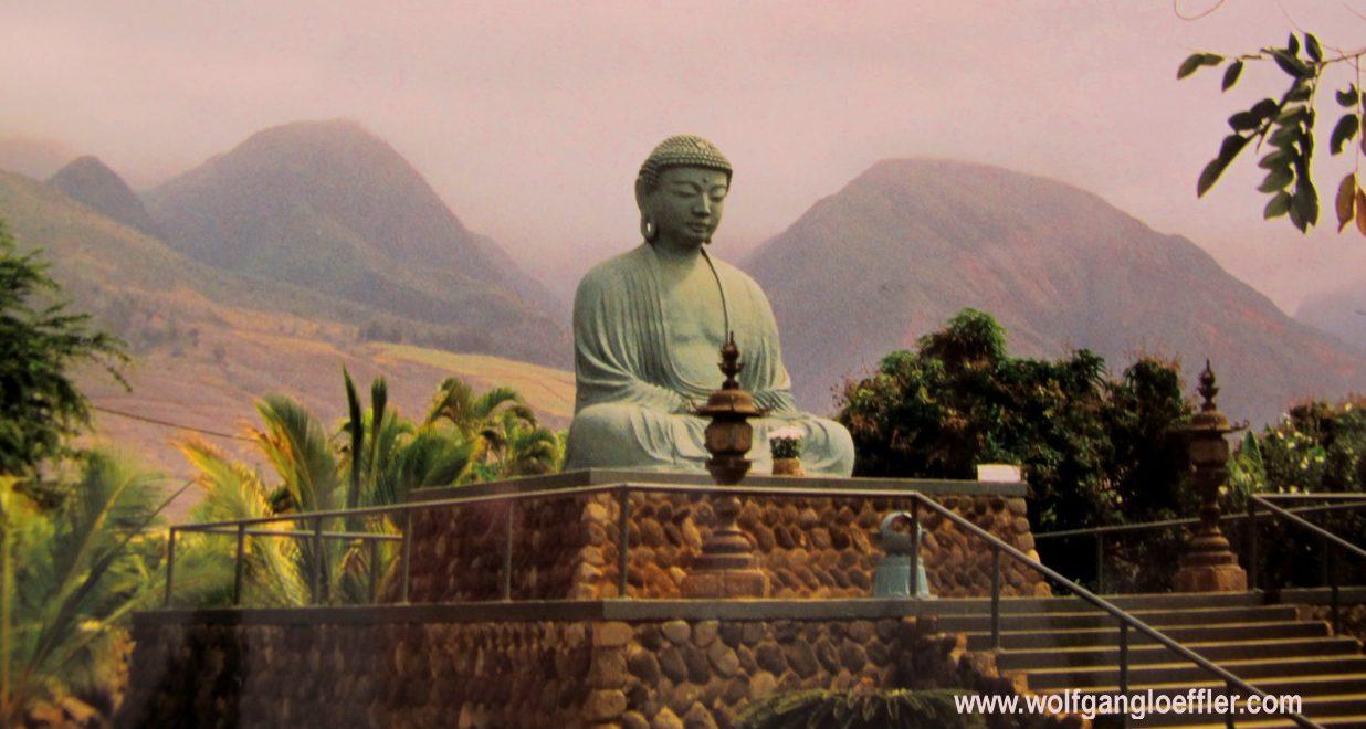 Buddhastatue vor bergigem Hintergrund