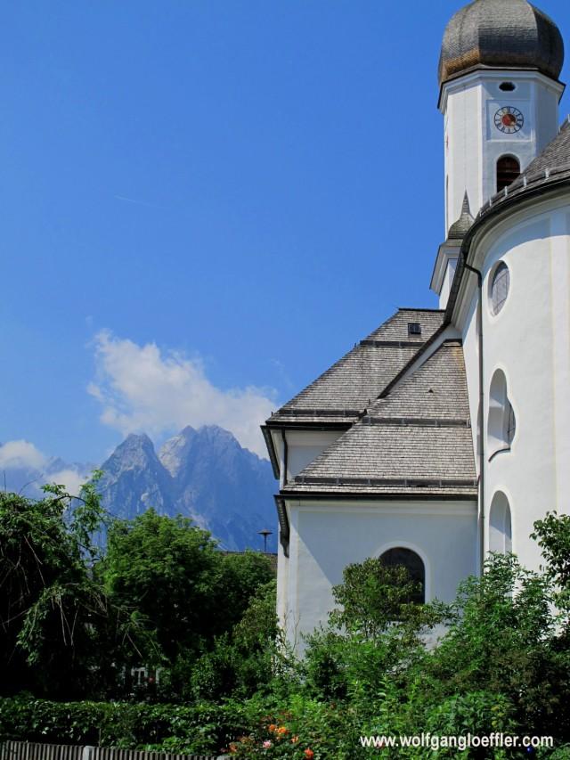Barocke Kirche in einem Garten mit Blick auf die Alpspitze