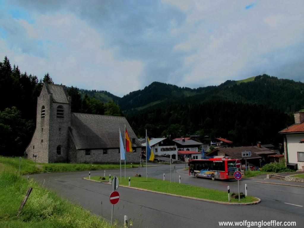Kirche im Dorf Spitzingsee mit Bergen im Hintergund