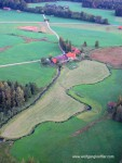 Ein einsaer Bauernhof von oben an einer frisch gemähten Wiese