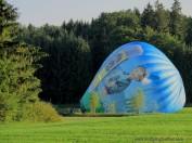 Ein Heißluftballon wird auf einer Wiese für den Start voerbeitet