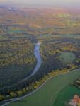 Blick von oben auf einen Fluss, der sich durch einen Wald schlängelt