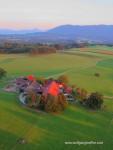 Luftaufnahme eines einsamen Bauernhofs vor Alpenpanorama