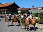 Fünf Frauen im Dirndl reiten auf gestriegelten Pferden