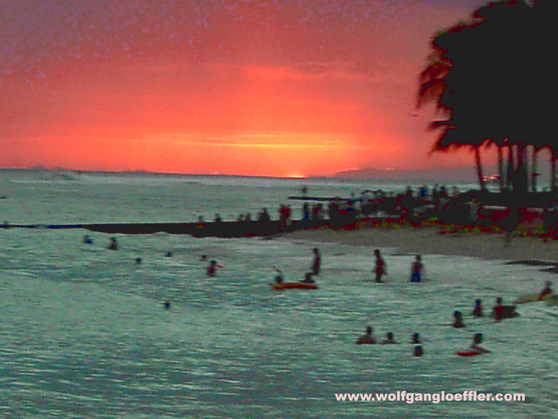 Badende Menschen im Meer beim Sonnenuntergang in Waikiki