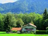 Einsames BAuernhaus am Wald mit Bergen im HIntergrund