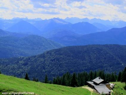 Blick von einem Berg über bewaldete Berge ins Karwendelgebirge
